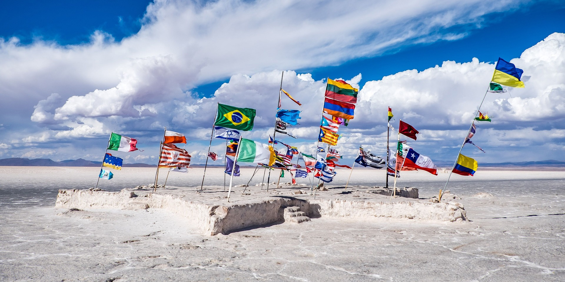Selection of world flags flap in the wind on the beach against a blue sky