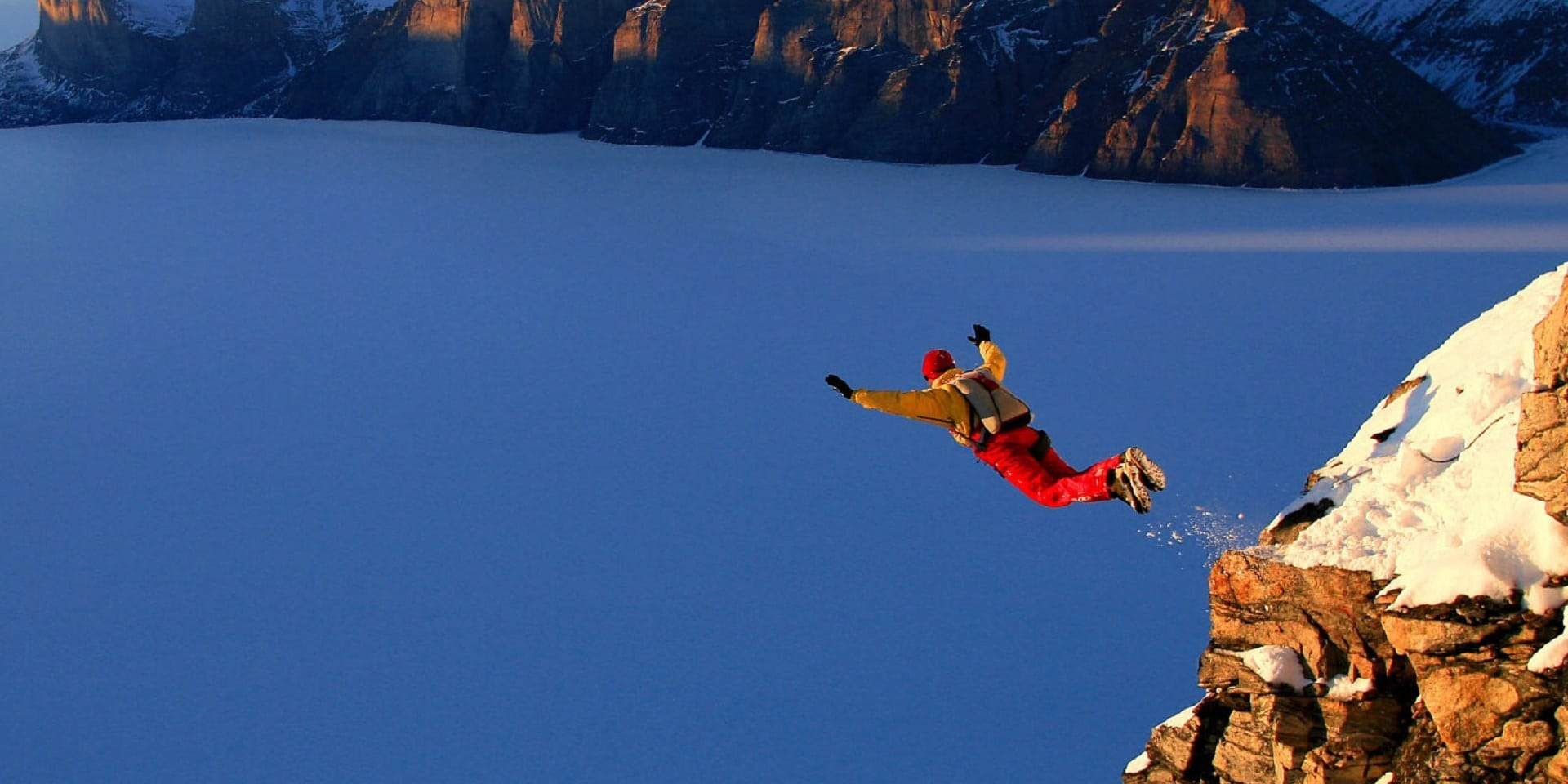 person base jumping off a cliff against a snowy mountain backdrop